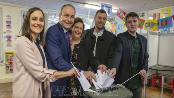 Lãnh đạo đảng đối lập Fianna Fail Michael Martin (thứ hai, bên trái) cùng gia đình bỏ phiếu. Ảnh: AFP/TTXVN