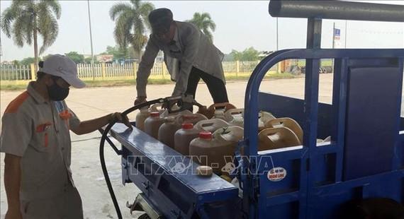 Người dân đổ xô đi mua xăng dầu tích trữ. Ảnh: TTXVN