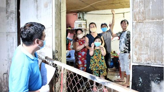 Ông Phạm Trung Kiên (trái), Chủ tịch UBND phường 7 quận Gò Vấp, đến từng nhà  trao giấy chứng nhận hoàn thành thời gian cách ly