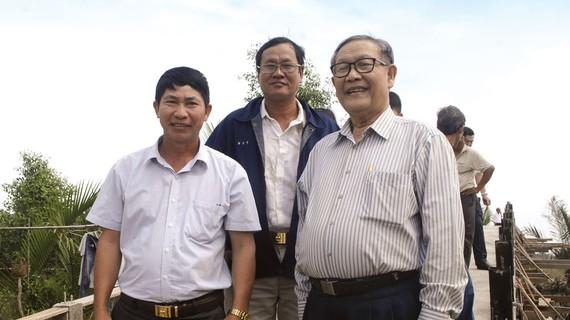 Ông Trịnh Văn Y (bên phải) đi kiểm tra một cây cầu sắp hoàn thành