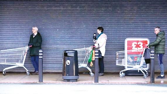 Người dân Anh giữ khoảng cách khi xếp hàng vào siêu thị