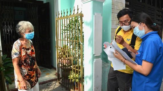 Bưu tá và chuyên viên UBND phường Tân Định (quận 1, TPHCM)  tới nhà chi trả chế độ ưu đãi người có công với cách mạng. Ảnh: VIỆT DŨNG