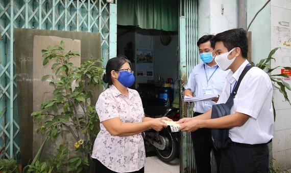 Trao tiền trợ cấp xã hội tận nhà cho người dân phường 9,  quận Phú Nhuận, TPHCM. Ảnh: DŨNG PHƯƠNG