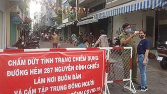 Đo thân nhiệt người dân ra vào khu chợ tự phát  hẻm 287 Nguyễn Đình Chiểu (phường 5 quận 3)