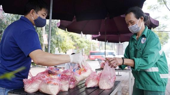 Người dân hoàn cảnh khó khăn đến nhận thực phẩm tại một điểm phát hàng từ thiện ở Hà Nội.  Ảnh: ĐỖ TRUNG