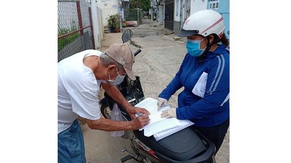 Công chức UBND phường Linh Trung, quận Thủ Đức  (bên phải) nhận hồ sơ hành chính và trả kết quả giải quyết  tại nhà người dân. Ảnh: KIỀU PHONG