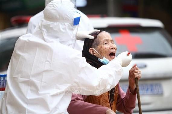 Lấy mẫu xét nghiệm virus SARS-CoV-2 cho người dân thôn Hạ Lôi, xã Mê Linh (huyện Mê Linh, Hà Nội). Ảnh: TTXVN