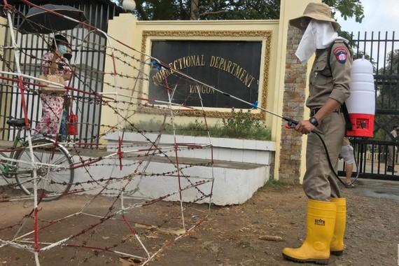 Nhân viên y tế phun khử khuẩn bên ngoài một nhà tù ở Myanmar. Ảnh: Reuters.