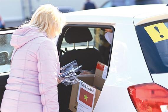 Một phụ nữ Nga ở thành phố Moscow nhận khẩu trang             do cộng đồng người Việt may tặng. Ảnh: VNA