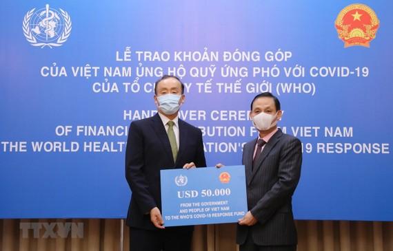 Thứ trưởng Bộ Ngoại giao Lê Hoài Trung trao tượng trưng số tiền 50.000 USD của Chính phủ và nhân dân Việt Nam đến Trưởng Đại diện Tổ chức Y tế Thế giới tại Việt Nam Kidong Park. Ảnh: TTXVN