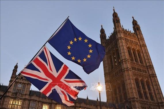 Quốc kỳ Anh và cờ Liên minh châu Âu bên ngoài tòa nhà Quốc hội Anh ở London. Ảnh: AFP/TTXVN
