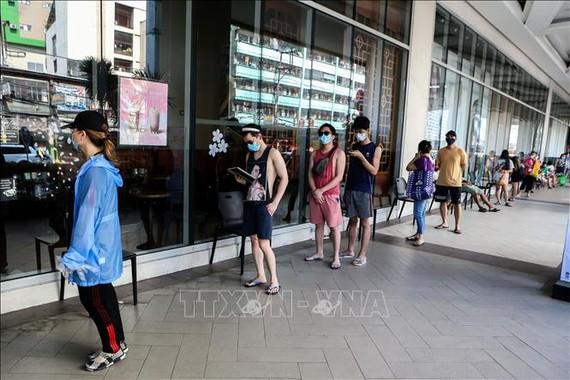 Dự báo kinh tế ở các nước đang phát triển sẽ giảm 2% trong năm nay. Người dân Philippines xếp hàng bên ngoài một cửa hiệu ở Manila. Ảnh: THX/TTXVN