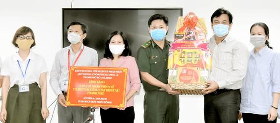 Đồng chí Nguyễn Thị Thu Hoài (thứ 3 từ trái sang) tặng quà Ban giám đốc Trung tâm Kiểm soát bệnh tật TPHCM
