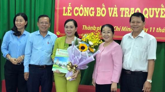 Đồng chí Võ Thị Dung trao quyết định và tặng hoa chúc mừng  đồng chí Nguyễn Thanh Xuân. Ảnh: THÁI PHƯƠNG
