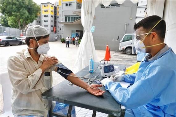 Nhân viên y tế lấy mẫu xét nghiệm COVID-19 tại khu nhà tập thể Toh Guan ở Singapore. Ảnh: THX/TTXVN