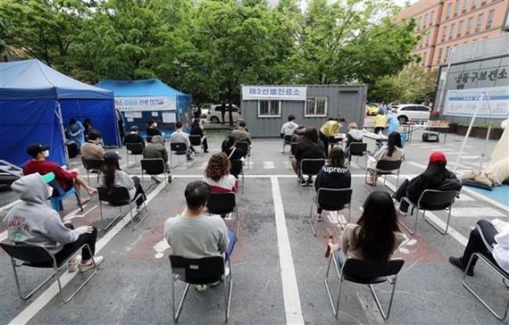 Người dân xếp hàng chờ xét nghiệm COVID-19 tại Seoul, Hàn Quốc. Ảnh: Yonhap/TTXVN