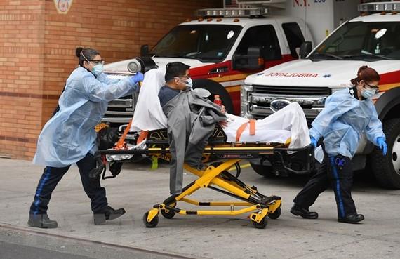 Nhân viên y tế chuyển bệnh nhân COVID-19 tới bệnh viện ở New York, Mỹ. Ảnh: AFP/ TTXVN
