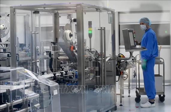 Nhân viên làm việc trên dây chuyền sản xuất vaccine phòng COVID-19 tại một công ty công nghệ sinh học ở thành phố Saint Petersburg, Nga. Ảnh: AFP/TTXVN