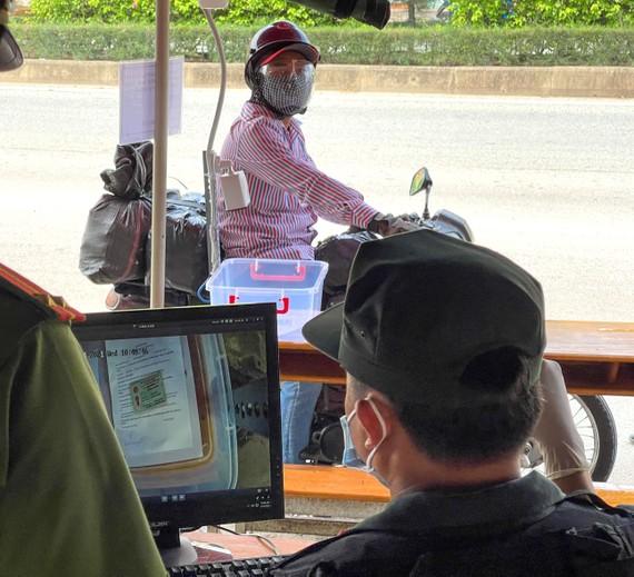"""Kiểm tra giấy tờ """"không chạm"""" bằng camera tại chốt kiểm soát dịch đầu cầu Phú Long. Ảnh: hoàng hùng"""