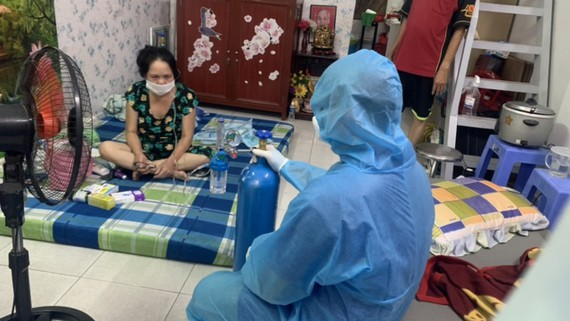 Một trường hợp F0 ở quận Bình Tân được hướng dẫn sử dụng bình oxy. Ảnh: MINH NGHĨA