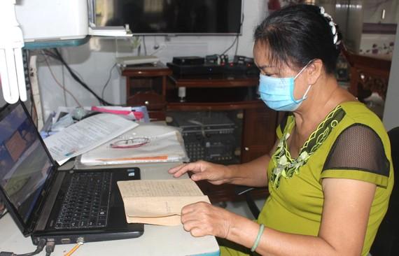 Bà Thuận đang xem lại nhật ký thời gian chiến đấu cùng Đội nữ pháo cối Xuân Lộc