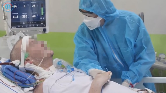 Phi công người Anh đã tỉnh, bắt tay nhân viên chăm sóc y tế. Ảnh cắt từ clip của Bệnh viện Chợ Rẫy