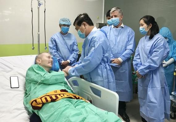 Chủ tịch UBND TPHCM Nguyễn Thành Phong thăm hỏi, động viên bệnh nhân thứ 91 – phi công người Anh tại Bệnh viện Chợ Rẫy, chiều 17-6-2020. Ảnh: HOÀNG HÙNG