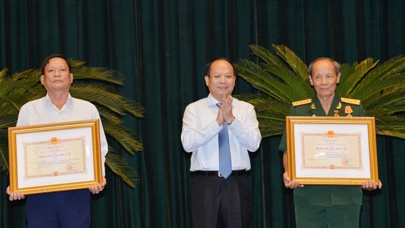 Ủy viên Trung ương Đảng, Phó Bí thư Thường trực Thành ủy TPHCM Tất Thành Cang trao tặng và chúc mừng các đồng chí nhận Huân chương Độc lập hạng Ba. Ảnh: VIỆT DŨNG