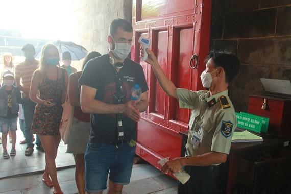 Đo thân nhiệt cho du khách trước khi vào tham quan Đại nội Huế