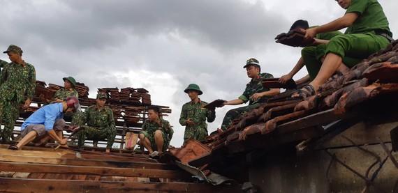 Lực lượng chức năng giúp người dân lợp lại mái nhà sau lốc xoáy