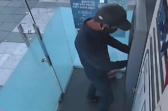 Nghi phạm thực hiện lắp đặt thiết bị trộm cắp thông tin tại cây ATM. Ảnh cắt lại từ clip