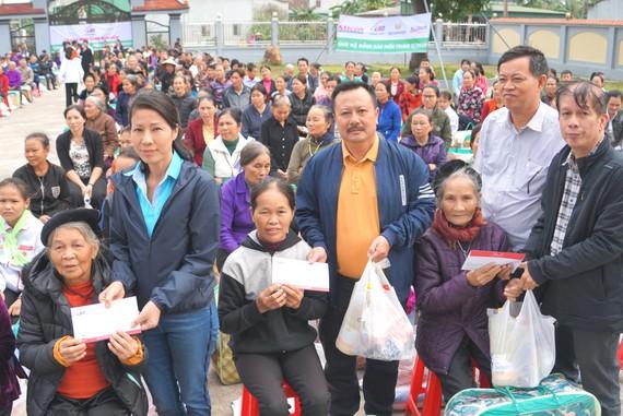 Đại diện Báo SGGP, Chủ tịch UBND xã Cẩm Thạch cùng các nhà tài trợ trao quà cho bà con vùng lũ ở xã Cẩm Thạch (huyện Cẩm Xuyên, tỉnh Hà Tĩnh)