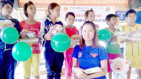 Chị Nguyễn Thị Như Ngọc (hàng đầu) trao quà cho trẻ có hoàn cảnh khó khăn