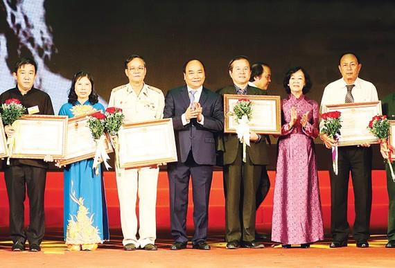 Thủ tướng Nguyễn Xuân Phúc trao bằng khen của Thủ tướng Chính phủ tặng các đại biểu  dự Hội nghị biểu dương người có công với cách mạng tiêu biểu toàn quốc