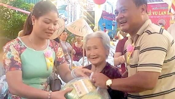 Vợ chồng anh Tú phát quà tặng người nghèo trong lễ Vu Lan tại chùa Phụng Ân                                           Ảnh: HOÀI NAM