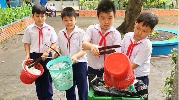 Học sinh Trường Tiểu học Lý Nhân Tông, quận 8 (TPHCM) thu gom rác  ở trường, thực hiện phân loại rác tại nguồn       Ảnh: THÀNH TRÍ