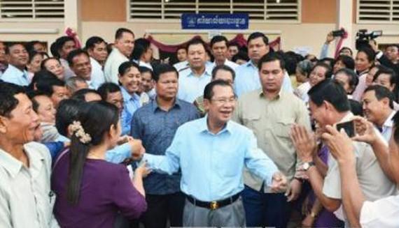 Đảng CPP cầm quyền của Thủ tướng Hun Sen (giữa) được dự báo sẽ tiếp tục giành được chiến thắng tại tổng tuyển cử sắp tới. Ảnh: KYODO/TTXVN