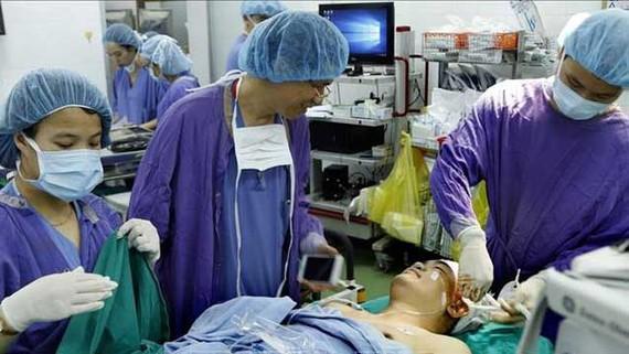 PGS.TS Đồng Văn Hệ, Phó Giám đốc bệnh viện Hữu nghị Việt Đức nói chuyện bình thường với bệnh nhân ngay trên bàn mổ. Ảnh: TTXVN
