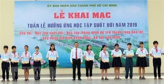 Các em học sinh được nhận học bổng khuyến học tại chương trình. Ảnh: TTXVN