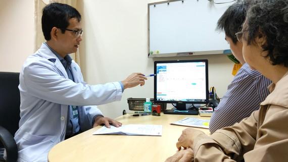 Bác sĩ Trần Ngọc Tài thăm khám và tư vấn cho bệnh nhân bị bệnh Parkinson.  Ảnh: HOÀNG HÙNG