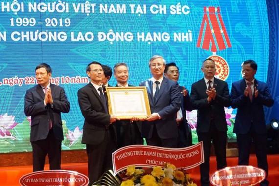 Thường trực Ban Bí thư Trần Quốc Vượng (phải)  trao Huân chương Lao động hạng hai do Chủ tịch nước  tặng Hội người Việt Nam tại Cộng hòa Czech. Ảnh: TTXVN