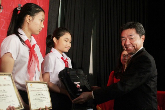 Ông Tatsuya Nakayama, Giám đốc Khối Sản xuất, Công ty Ajinomoto Việt Nam trao học bổng cho các em học sinh