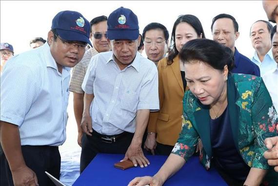 Chủ tịch Quốc hội Nguyễn Thị Kim Ngân xem công nghệ cho cá ăn ứng dụng qua hệ thống vi tính tại vùng nuôi cá tra ứng dụng công nghệ cao. Ảnh: TTXVN