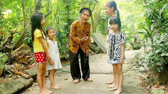 Nghệ nhân ưu tú Nguyễn Thị Vẫy dạy hát Trống quân cho thiếu nhi ngay tại vườn nhà mình