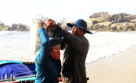 Người thân của ngư dân làng lưới thúng Trung Lương mang cá đi bán tại các phiên chợ gần làng