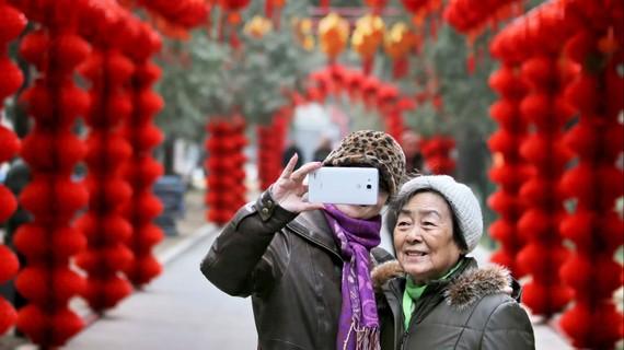 Dùng smartphone selfie trong hội chợ xuân ở Bắc Kinh