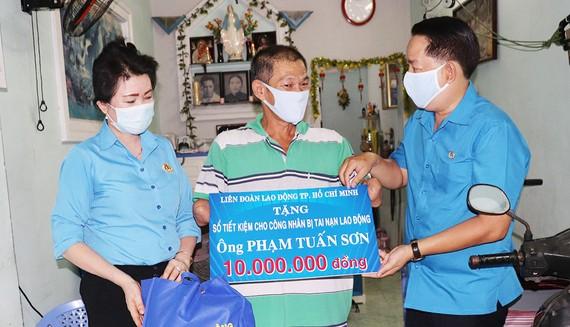 Đồng chí Kiều Ngọc Vũ, Phó Chủ tịch LĐLĐ TPHCM  (bên phải) trao tặng công nhân bị tai nạn lao động sổ tiết kiệm