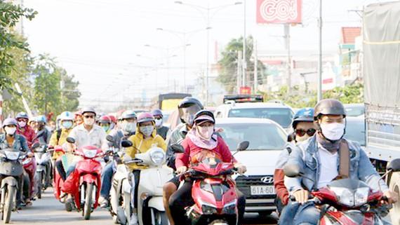 Người đi xe gắn máy chen chúc chờ qua cầu Rạch Miễu. Ảnh: HUY PHÚC