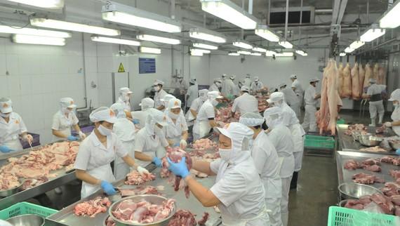 Pha lóc thịt heo phục vụ nhu cầu tiêu dùng trong nước tại Công ty Vissan. Ảnh: CAO THĂNG