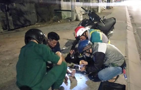 Các thành viên Đội cứu trợ giao thông quận 12 giúp đỡ người bị té xe dọc đường